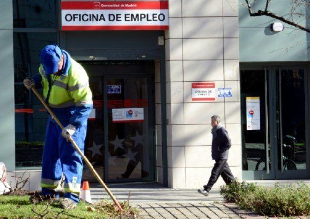 Un operario municipal limpia una zona verde frente a una oficina de