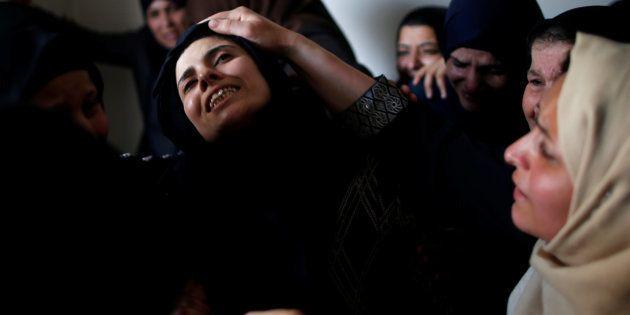 La madre de Azam Ewidah, un chico de 15 años muerto por disparos de Israel, llora durante su funeral,...