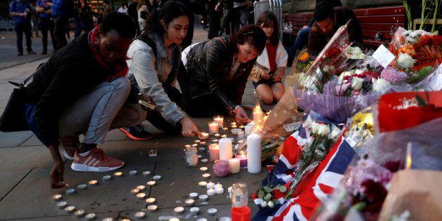 Un grupo de mujeres coloca velas y flores en el memorial por las víctimas, en el centro de Manchester,...