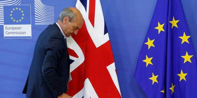 Un trabajador pasa junto a las banderas de Reino Unido y la UE en