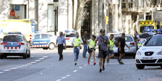 Un grupo de viandantes corren por Las Ramblas, mientras los agentes tratan de despejar la zona tras el...