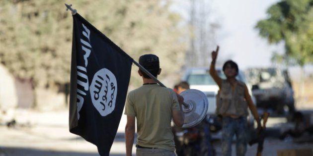 Un rebelde sirio se lleva como trofeo una bandera del ISIS de la villa de Akhtarin, al norte de Alepo...