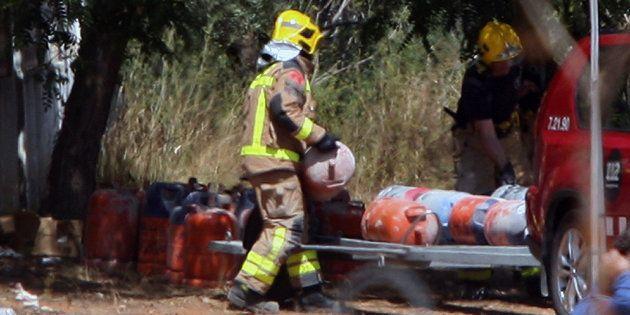Los Bomberos trasladan las bombonas de butano encontradas en la casa donde se produjo la explosión en...