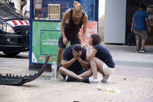 Varios jóvenes permanecen en shock junto a los restos de la furgoneta con la que se cometió el atentado,...