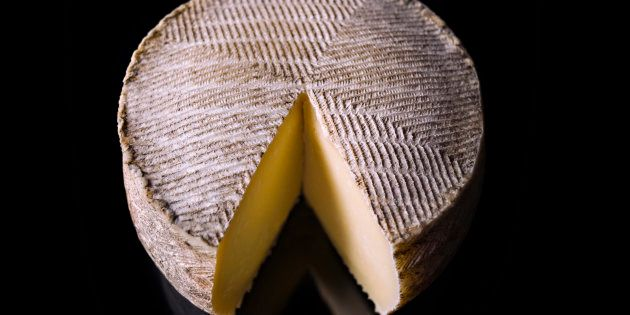 Wheel of manchego cheese on black