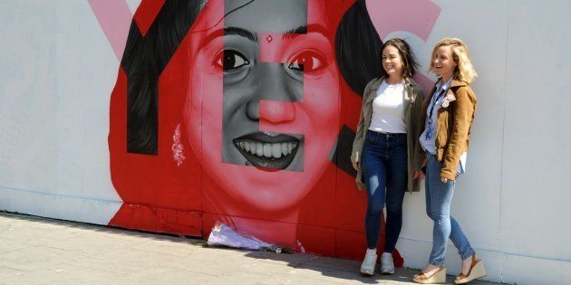 Dos mujeres junto a un mural de la campaña a favor del aborto, en