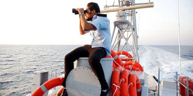 Un miembro de la Guardia Costera libia trata de divisar embarcaciones de migrantes en el Mediterráneo,...