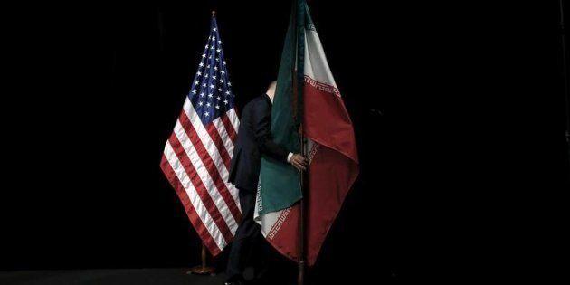 Un empleado retira las banderas de EEUU e Irán tras la firma del acuerdo sobre el programa atómico de...
