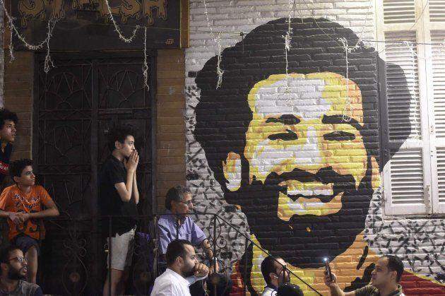 Aficionados egipcios reaccionan a la lesión de Salah, junto a un mural del jugador, en El