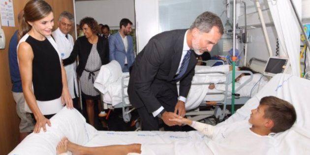 Los reyes Felipe y Letizia, saludando a uno de los niños heridos, en su visita al Hospital del Mar de