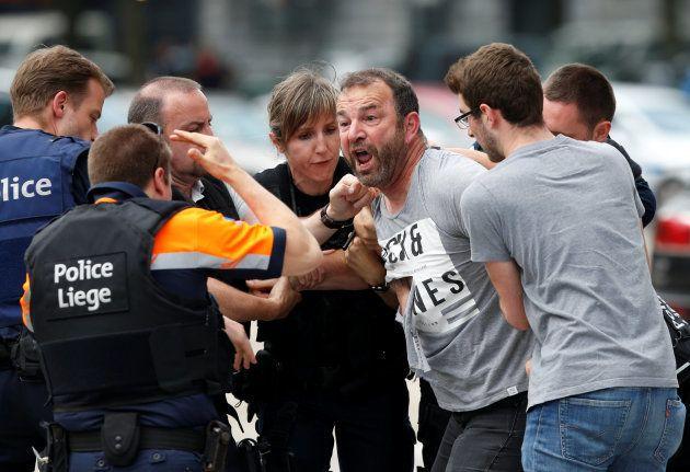 Un hombre es atendido por los policías desplegados en la zona, tras conocerse la muerte de tres personas...