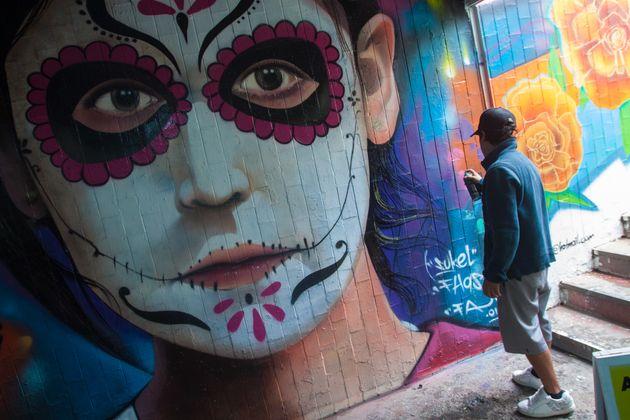 Jóvenes grafiteros plasman sus diseños en un bajopuente de Calzada de Tlalpan, en CDMX, como parte de...