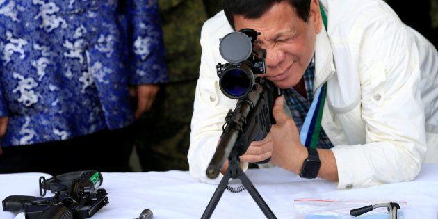 El presidente filipino, Rodrigo Duterte, chequea un rifle cedido por China, el pasado junio cerca de...