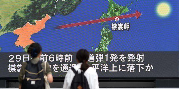 Varias personas ven en la televisión la trayectoria del nuevo misil lanzado por Corea del