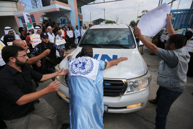 Un grupo de palestinos trata de bloquear el paso de los coches de la ONU, en uno de los cuales viajaba