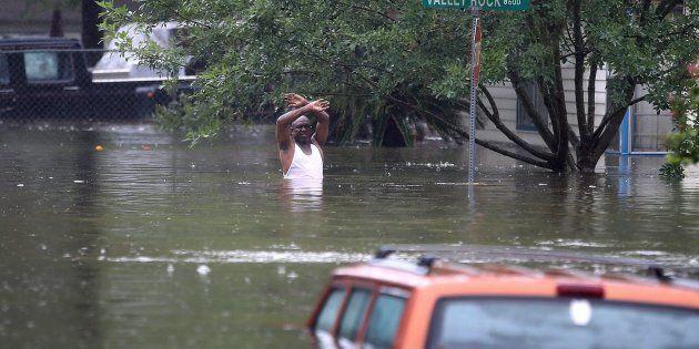 Un hombre hundido hasta la cintura en agua sucia gesticula hacia el equipo de rescarte que se aproxima...