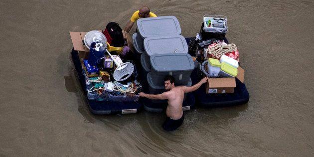 Un hombre traslada sus pertenencias tras verse afectado por el paso de la tormenta tropical