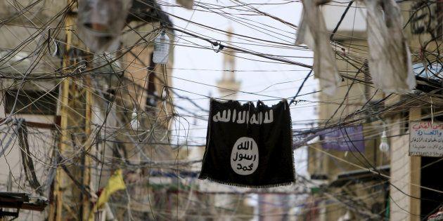 Una bandera del ISIS ondea entre alambres y cables de la luz en el campo de refugiados de Ain al-Hilweh,...