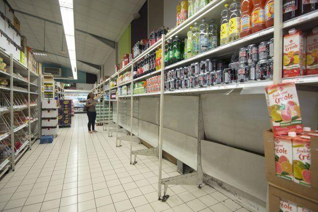 Una mujer camina en un supermercado donde se han vendido todas las botellas de agua para la preparación...
