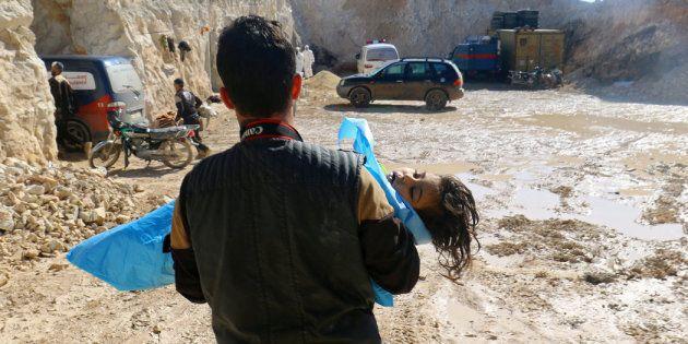 El cuerpo de un menor es trasladado por un fotógrafo tras el ataque con armas químicas sobre Jan Shijún,...