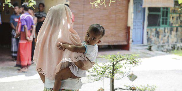 Una refugiada perteneciente a los rohingyas sostiene a su hijo en un refugio en Medan
