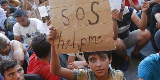 Un niño refugiado pide ayuda con un cartel de cartón, mientras espera en las vías de la estación de Budapest...