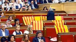 Una diputada retira las banderas de España de los escaños vacíos del