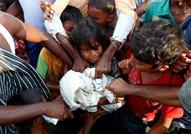 Un grupo de refugiados rohingya pugna por la comida que varias ONG les han llevado tras tocar tierra...