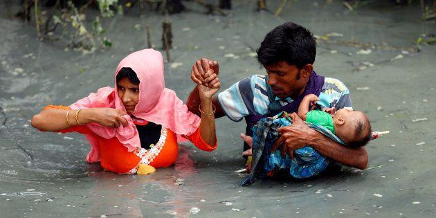 Una pareja de refugiados rohingyas y su bebé cruzan el río Naf en Teknaf,