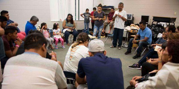 Un grupo de gente forma un círculo para rezar en una clase del colegio Pizzo Elementary de Tampa, un...