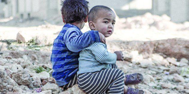 Esraa, de cuatro años y su hermano Waleed, de tres, sentados a las afueras de un centro de desplazados,...
