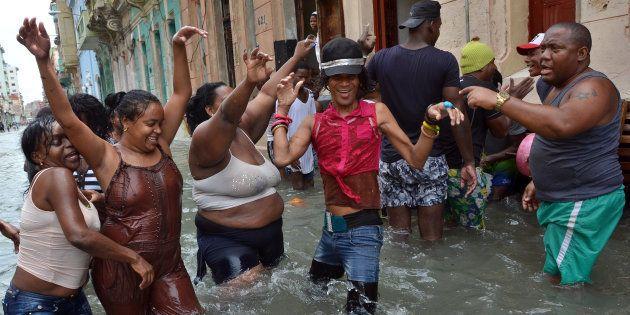 Vecinos de La Habana (Cuba) bailan en mitad de la calle anegada, tras el paso del