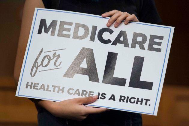 Un miembro del público sujeta una pancarta con el lema de Sanders para una sanidad