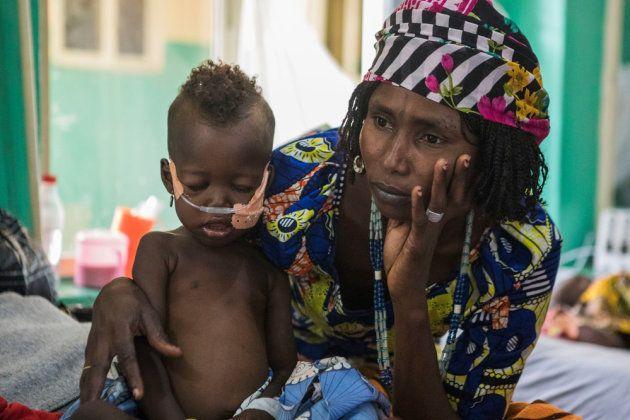 Una mujer mira al infinito con su hijo en brazos en el hospital comandado por MSF en Gwoza,