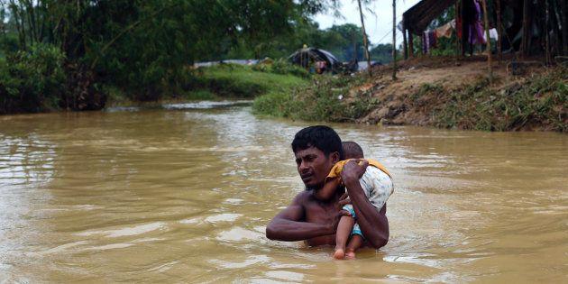 Un refugiado rohingya cruza un río con un bebé en brazos en Cox's Bazar, Bangladés, el 18 de septiembre...