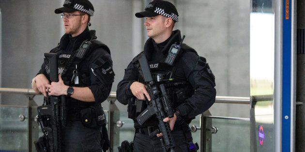 Dos policías armados patrullan los alrededores del lugar del