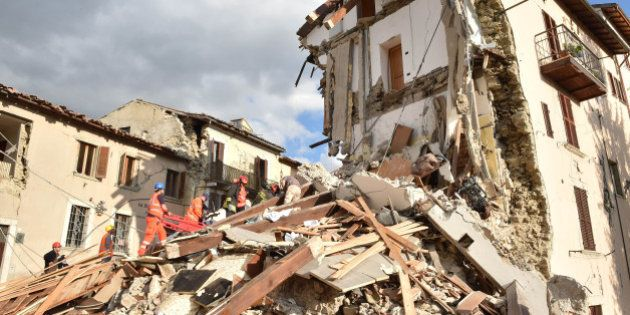 PERUGIA, ITALY - AUGUST 24: Rescuers clear debris while searching for victims in damaged buildings on...