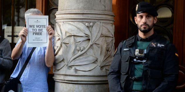Un hombre sostiene un cartel proreferéndum junto a un agente de la Guardia Civil frente a la Consellería...