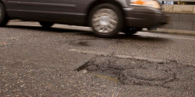 Downtown traffic passes a pothole in Portland, Ore., Thursday, Feb 11, 2010. If you live in Portland...