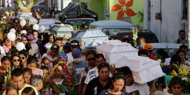 Un grupo de gente desfila por las calle de Atzala (Puebla) portando los ataúdes de varias víctimas del