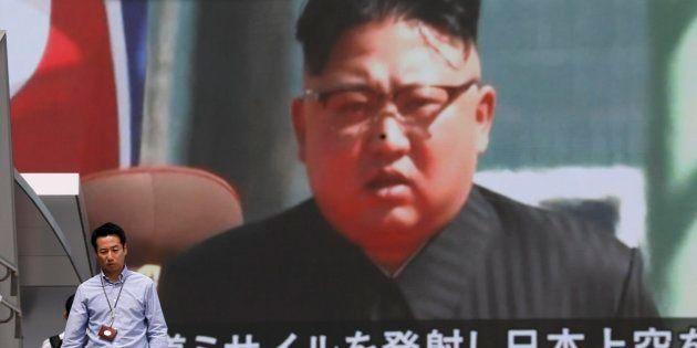 Los peatones caminan bajo un monitor a gran escala que muestra al líder norcoreano Kim