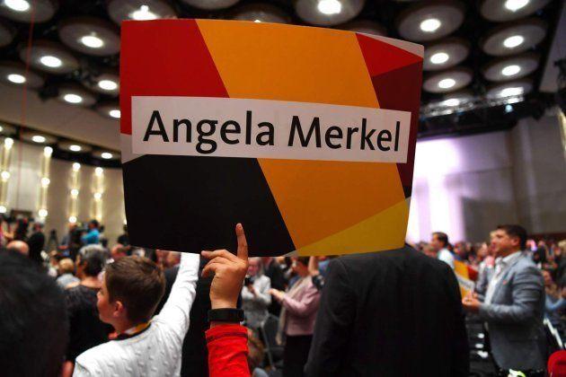 Seguidores de Merkel sujetan carteles con su