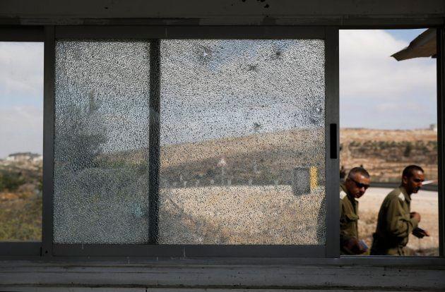 Miembros de las Fuerzas de Seguridad israelíes caminan junto a una ventana rota en el lugar donde se...