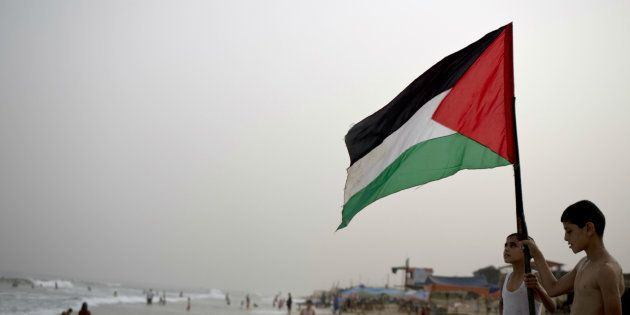 Unos niños ondean la bandera palestina en una playa de Gaza, en una imagen de septiembre de