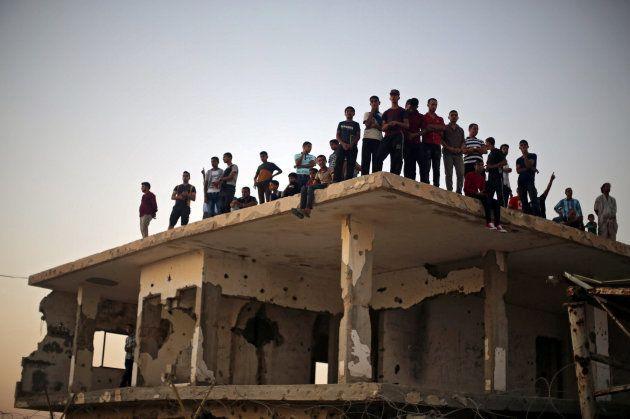 Un grupo de gazatíes espera a que sus familiares logren pasar el cruce de Rafah con Egipto, sobre un...