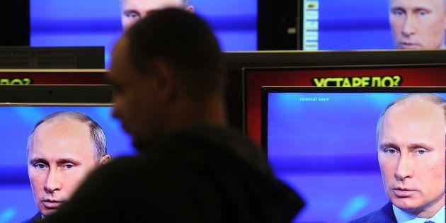 Un cliente pasa delante de varias televisiones con la imagen de Vladimir Putin en Moscú, en abril de...
