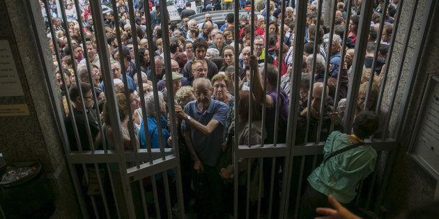 Numerosas personas hacen cola en el instituto Moisés Broggi de Barcelona para votar en el referéndum...