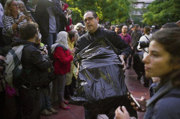Una persona entra con un paquete en la Escola Industrial de Barcelona con una de las urnas envuelta en...