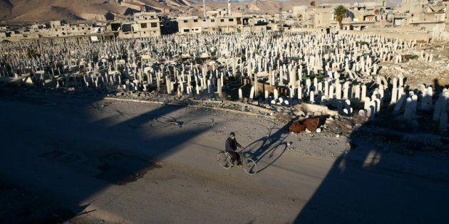 Un civil pasa en bicicleta ante el cementerio de Douma, barrio rebelde de