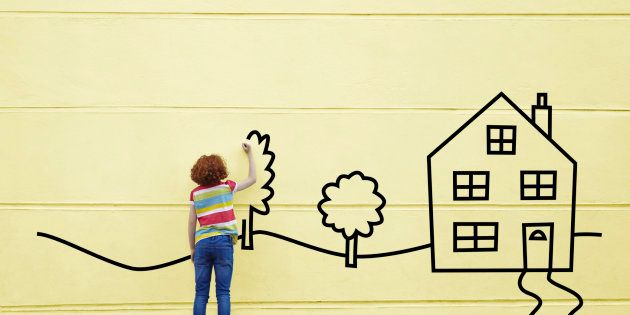 Girl drawing a house and trees onto a